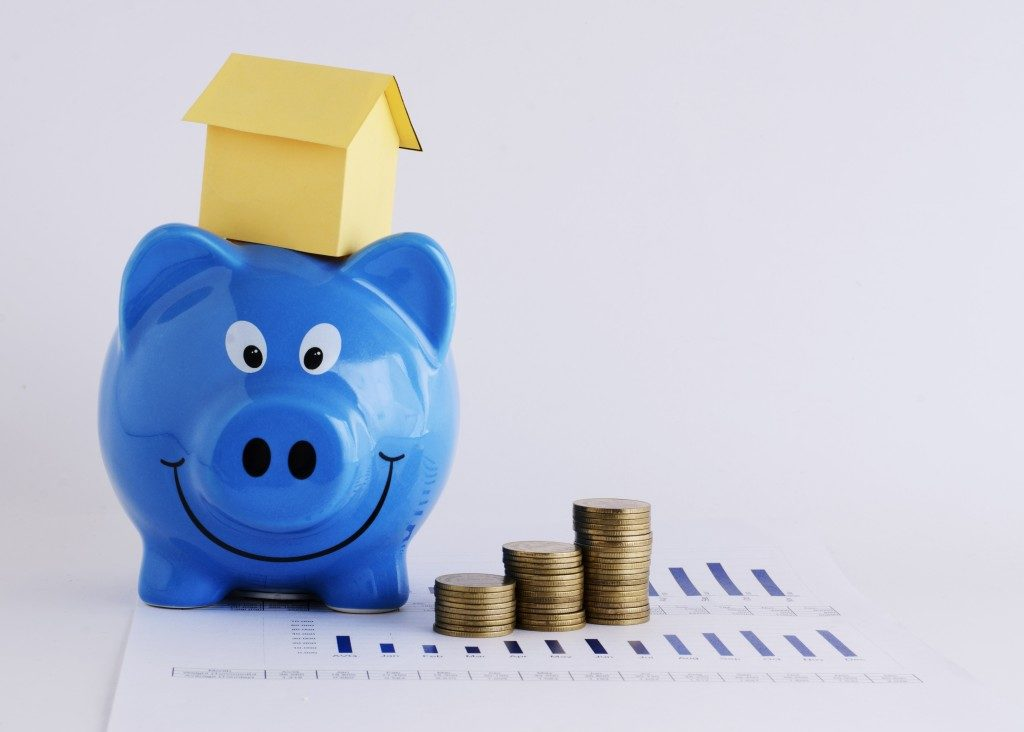 Piggy bank and coins with house figures