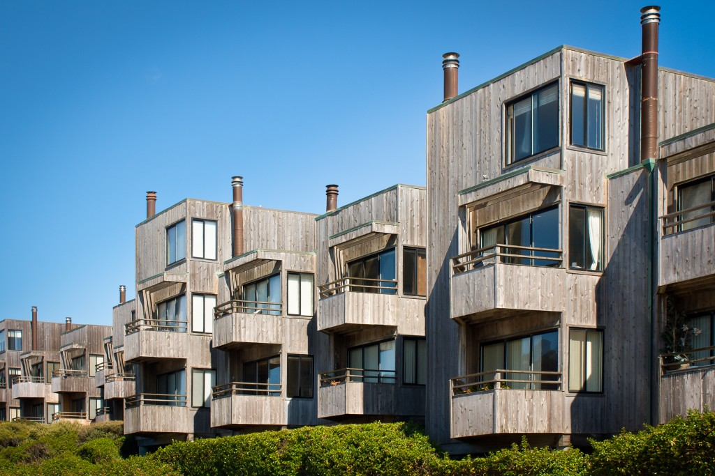 A cluster of modern style townhomes with balconies and wood siding