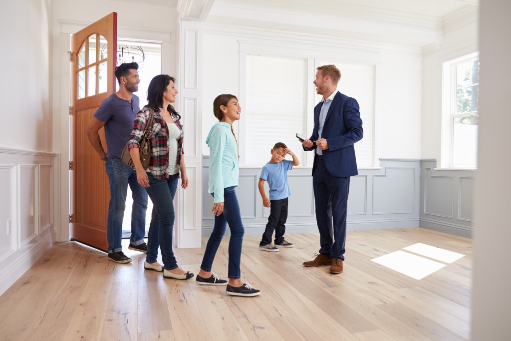 realtor with family looking at a house